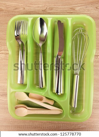 Green plastic cutlery tray with checked cutlery and wooden spoons on wooden table