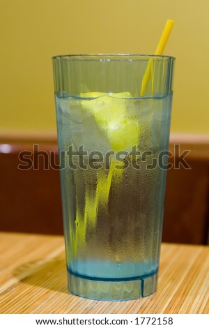 Green plastic glass filled with water, with a yellow straw and slice of lemon.  Glass is sitting on a wooden restaurant table. - stock photo