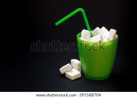 Green plastic glass with straw full of sugar and sugar cubes on black background. Concept image for too much sugar in sodas, juices, beverages, soft and fizzy drinks. Copy space - stock photo
