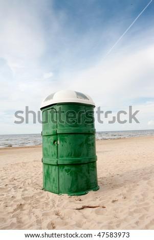 Green plastic portable toilet in the sandy beach - stock photo