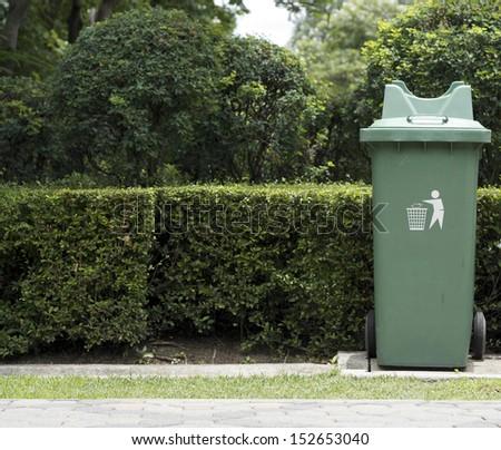 Green plastic recycle bin in park - stock photo