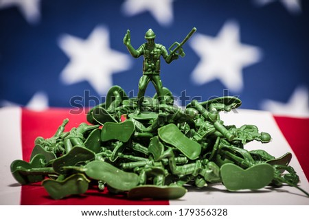 Green plastic soldiers on American flag background victorious on pile - stock photo