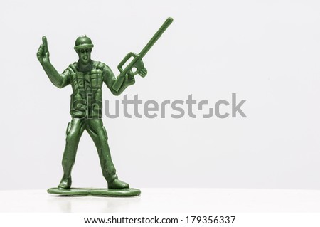 Green plastic soldiers on white background with gun