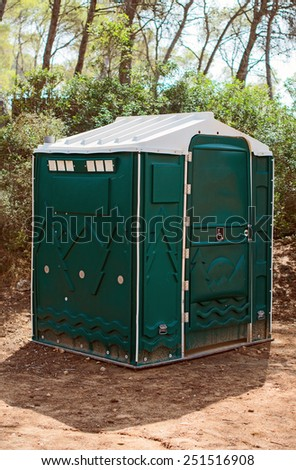 Green plastic toilet booth in the forest. - stock photo