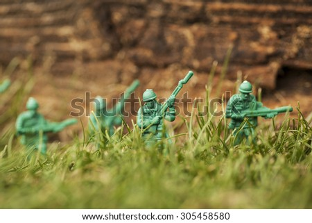 Green plastic toy soldier army unit walking through the overgrown grass. Selective focus and wooden textured background  - stock photo