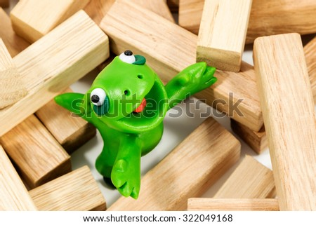 Green plasticine creature looking up standing on a block of wood - stock photo