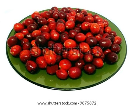 Green plate full of bright red cranberries isolated over a white background
