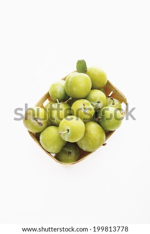 Green plums in a basket