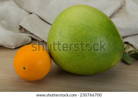Green pomelo and orange on the wood background - stock photo