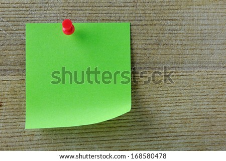 Green post it note with red push pin on a wooden background - stock photo