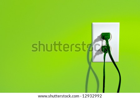 Green power cords in electric outlet on a green colored wall - green energy concept