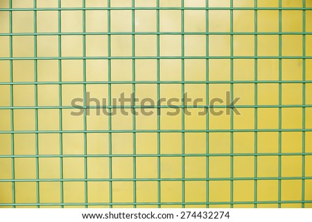 Green Protective metallic grid on a yellow background - stock photo