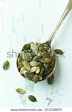 Green pumpkin seeds on an old spoon - stock photo