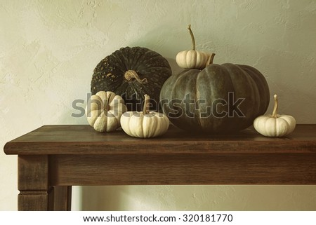 Green pumpkins and small gourds on wooden table  - stock photo