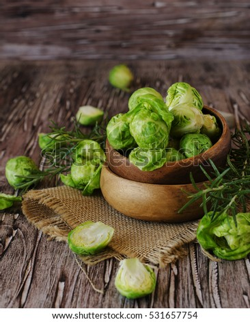 Green raw Brussels sprouts in a wooden bowl on a rustic wooden table, selective focus