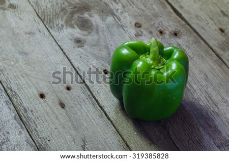 Green raw pepper on grey wooden background - stock photo