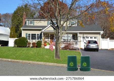 Green recycle, reuse, reduce, trash container Beautiful Cape Cod Home Autumn clear blue sky day residential neighborhood USA - stock photo