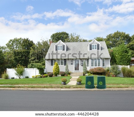 Green recycle, reuse, reduce, trash container Beautiful Gray Suburban Home Landscaped Sunny Blue Sky Clouds Residential Neighborhood USA