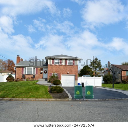 Green recycle, reuse, reduce, trash container Beautiful Suburban Brick Snout style home landscaped yard residential neighborhood USA blue sky clouds
