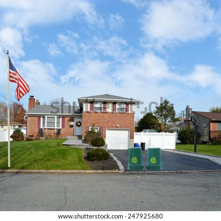 Green recycle, reuse, reduce, trash container Beautiful Suburban Brick Snout style home landscaped yard residential neighborhood USA blue sky clouds - stock photo