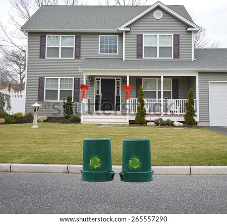 Green recycle, reuse, reduce, trash container Suburban McMansion style home overcast day residential neighborhood USA - stock photo