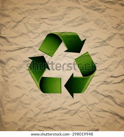 Green recycle symbol on crumpled cardboard,