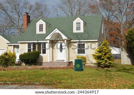 Green recycle trash container Suburban Cape Cod style home autumn day residential neighborhood USA
