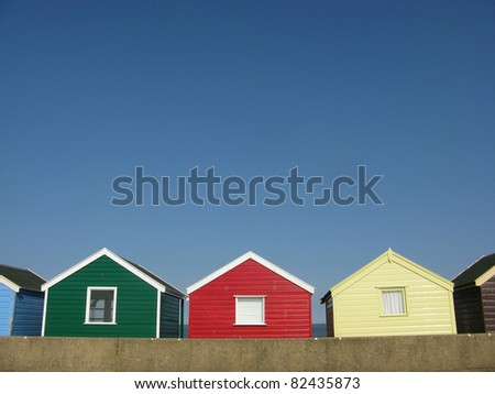 Green, red and yellow beach huts on sunny day in Southwold, Suffolk, England, UK - stock photo