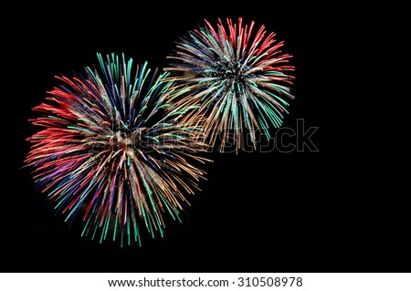 Green red blue white golden fireworks display on dark sky background - stock photo