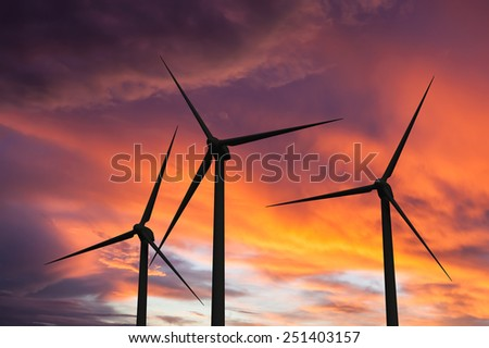 Green renewable energy concept - wind generator turbines in sky on sunset