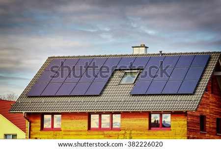 Green Renewable Energy. Photovoltaic Panels on the Roof. A completely solar energy powered house. Old house adapted for solar energy panels. - stock photo