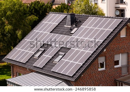 Green Renewable Energy with Photovoltaic Panels on the Roof. - stock photo