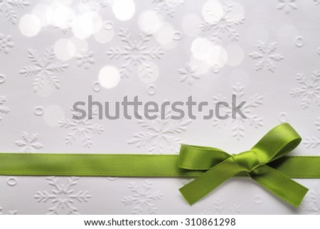 Green ribbon bow with bokeh,Paper textured background. - stock photo