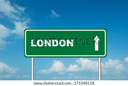 Green road sign board with straight direction to  London with sky background - stock photo