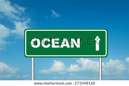 Green road sign board with straight direction to Ocean with sky background - stock photo
