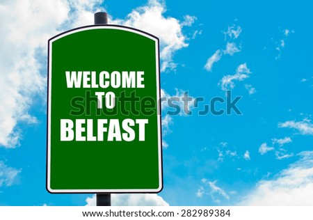 Green road sign with greeting message WELCOME TO BELFAST isolated over clear blue sky background with available copy space. Travel destination concept  image - stock photo