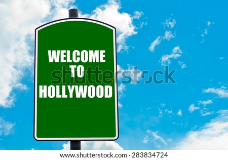Green road sign with greeting message Welcome to HOLLYWOOD isolated over clear blue sky background with available copy space. Travel destination concept  image - stock photo
