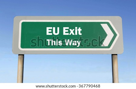 Green road sign with the message of an EU Exit This Way concept against a blue sky background  - stock photo