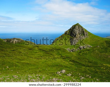 Green rocky hills on the Isle of Skye in Scotland with blue ocean in the background. - stock photo