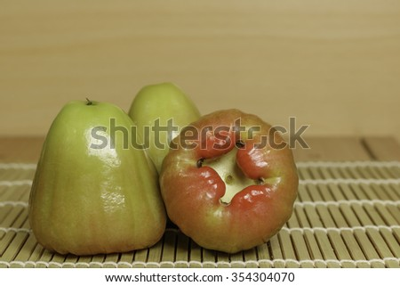 Green rose apple on grille bamboo and plywood background - stock photo