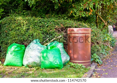 Green rubbish bags next to a brown bin for collection - stock photo