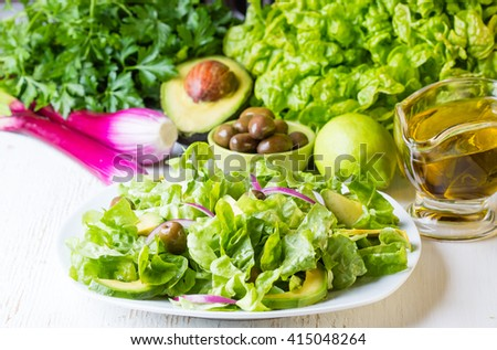 Green salad and ingredients - lettuce, avocado, olives, oil, herb and onion on white background. Vegetarian or healthy eating concept - stock photo