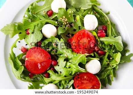 Green salad made with  arugula, tomatoes, cheese mozzarella balls and sesame  on plate, close-up