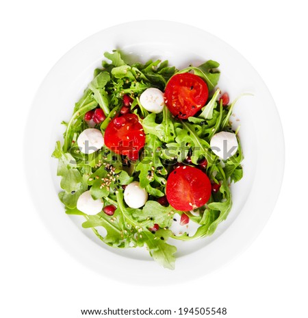Green salad made with  arugula, tomatoes, cheese mozzarella balls and sesame  on plate, isolated on white - stock photo