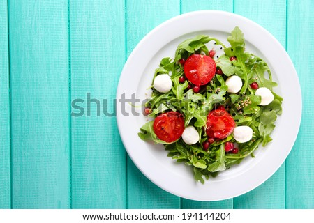 Green salad made with  arugula, tomatoes, cheese mozzarella balls and sesame  on plate, on color wooden background - stock photo