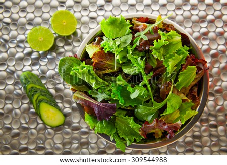 Green salad Mediterranean green and red lettucce spinach and cucumber on modern stainless steel - stock photo