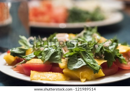 Green salad served with mango and tomatoes - stock photo