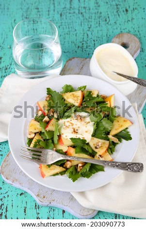 Green salad with apples, walnuts and cheese on color wooden background