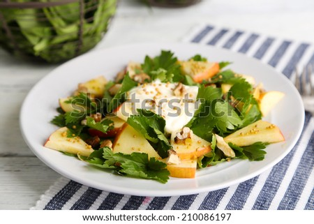 Green salad with apples, walnuts and cheese on wooden background