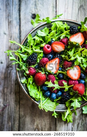 Green salad with arugula and berries - stock photo